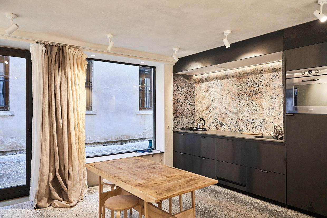 Kitchen with recuperated marble from an ancient Abbey near St Marc's Square. When the kitchen counter is covered the space transforms into a gallery. Photo by Paulina Westerlind.