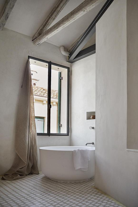 StudioGiardini's master bedroom and bathroom with a triangular shower and a round bathtub. Photo by Paulina Westerlind